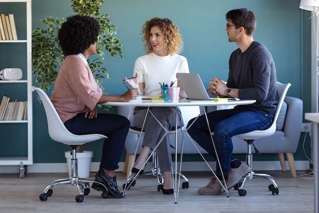 Foto de jovens empresários casuais trabalhando e conversando sobre o novo projeto juntos no escritório.