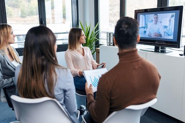 Foto de jovens empresários inteligentes trabalhando e falando sobre o novo projeto enquanto fazem uma videochamada com o diretor da empresa em um local de coworking.