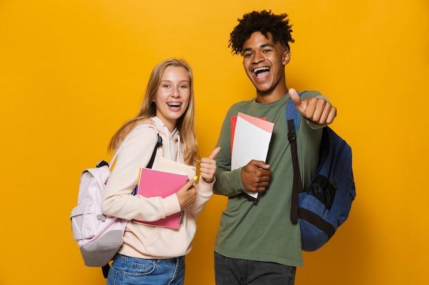 Foto de jovens estudantes rapaz e garota de 16 a 18 anos vestindo mochilas, sorrindo e segurando cadernos, isolados sobre fundo amarelo