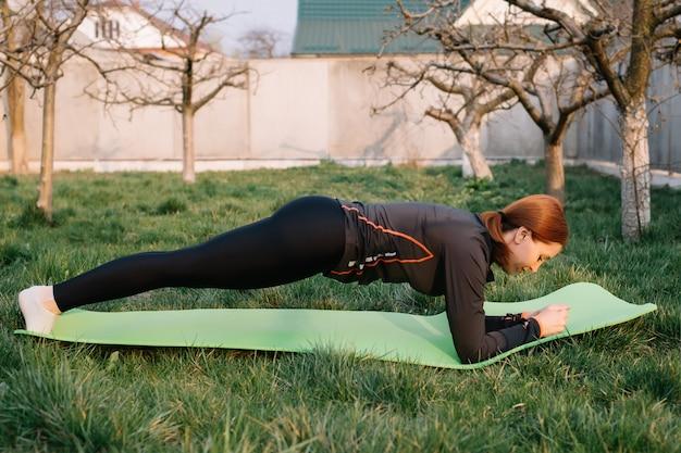 Foto de lado de perfil de comprimento total de mulher adulta fazer exercício de prancha