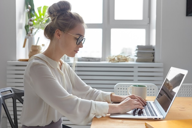 Foto de lado de séria na moda jovem empresária europeia usando uma blusa branca elegante e óculos redondos digitando em um dispositivo eletrônico genérico, verificando e-mail, escrevendo carta comercial