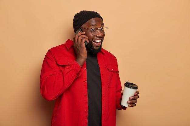 Foto de lado de um cara feliz de pele escura fazendo uma ligação telefônica, bebendo café para viagem