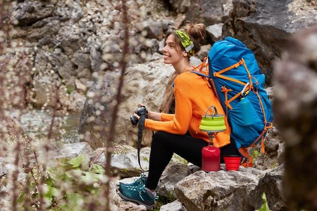 Foto de lado de um turista ativo fazendo uma pausa depois de passear, sentado na pedra, segurando uma câmera profissional