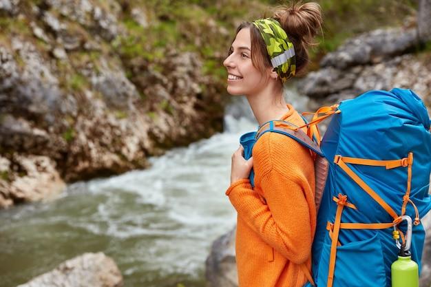 Foto de lado de um turista feliz passeando perto do riacho, com foco distante