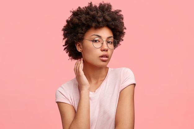 Foto de lado de uma adorável jovem com pele escura, parece séria e confiante, mostra sua beleza natural, posa para uma revista de moda, usa óculos redondos e camiseta casual