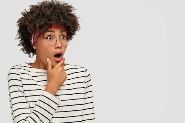 Foto de lado de uma jovem afro de pele escura espantada segurando a mão no queixo