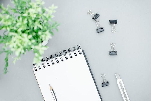 Foto de lápis, clipes de papel e bloco de notas em um fundo abstrato cinzento