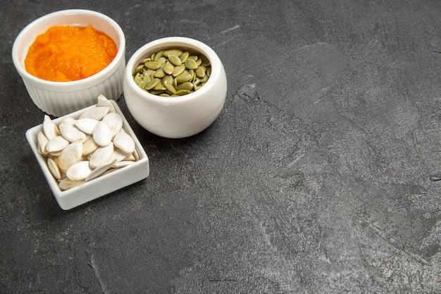 Foto de laranja madura com sementes de abóbora com sementes na cor de fundo cinza