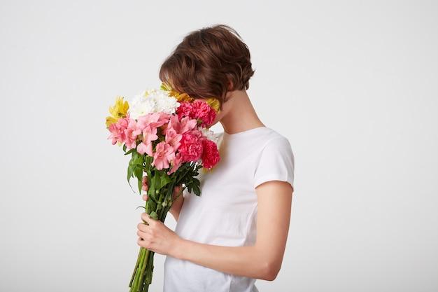 Foto de linda garota de cabelos curtos, segurando um buquê de flores coloridas, apreciando o cheiro, em pé sobre um fundo branco.