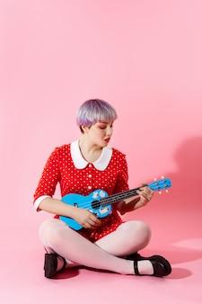 Foto de linda garota dollish com cabelo violeta curto curto, vestido vermelho, tocando ukulele azul sobre parede rosa