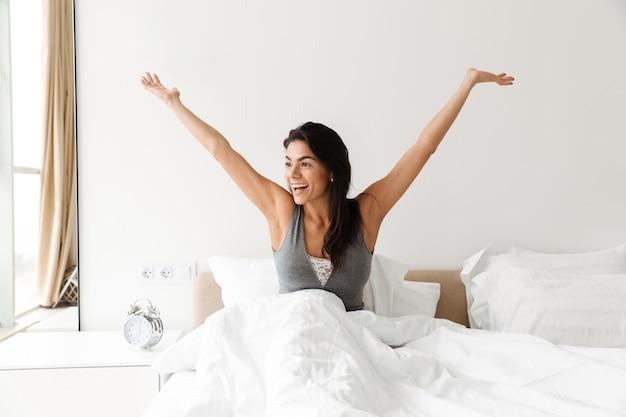 Foto de linda mulher bonita, acordando e regozijando-se de manhã, enquanto está sentado na cama com roupa de cama limpa branca no quarto