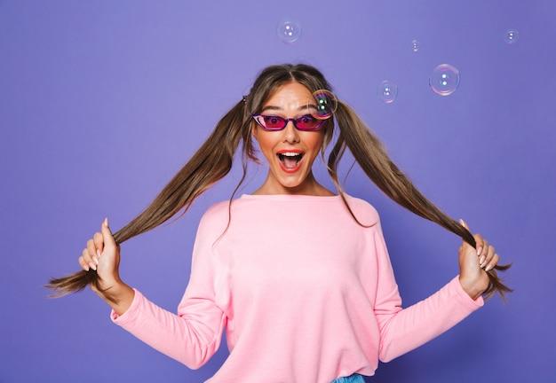 Foto de linda mulher caucasiana em moletom com óculos de sol da moda, se divertindo e tocando seus rabos de cavalo