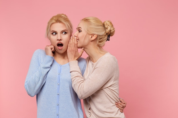 Foto de lindas gêmeas loiras, a menina conta para a irmã a incrível notícia sobre a qual a segunda abriu a boca de surpresa, fica sobre fundo rosa.
