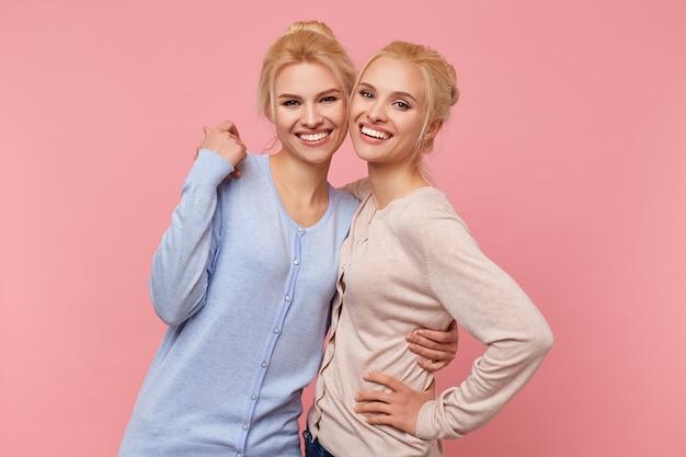 Foto de lindas irmãs gêmeas louras em casacos de lã idênticos de cores diferentes, se abraçando, felizes e divertidas, sorrisos largos sobre fundo rosa.