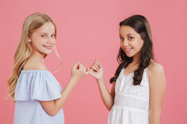 Foto de lindas meninas de 8 a 10 anos usando vestidos enganchando os dedinhos uma da outra em conciliação ou amizade, isolada sobre um fundo rosa