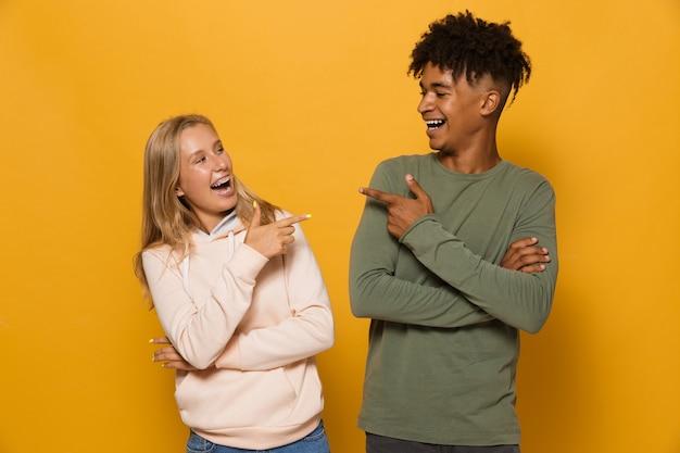 Foto de lindos alunos, homem e mulher, de 16 a 18 anos com aparelho dentário rindo um do outro, isolado sobre um fundo amarelo