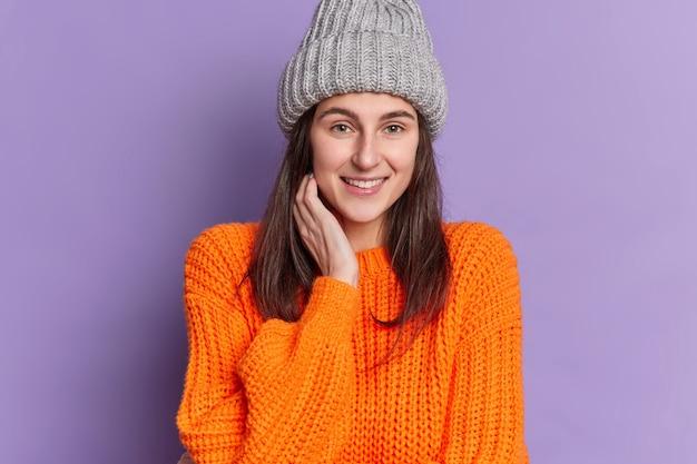 Foto de lindos sorrisos de garota milenar agradavelmente mantém a mão perto do rosto vestida com roupas de inverno de malha tem conversa casual com um amigo feliz por ter o fim de semana.