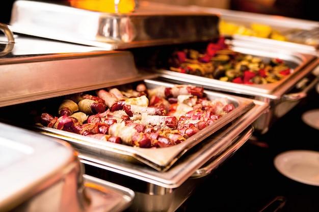 Foto de linguiças fritas como lanche em uma mesa de bufê