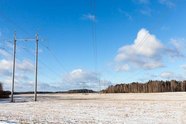 Foto de linhas de alta tensão no inverno. céu azul e neve branca
