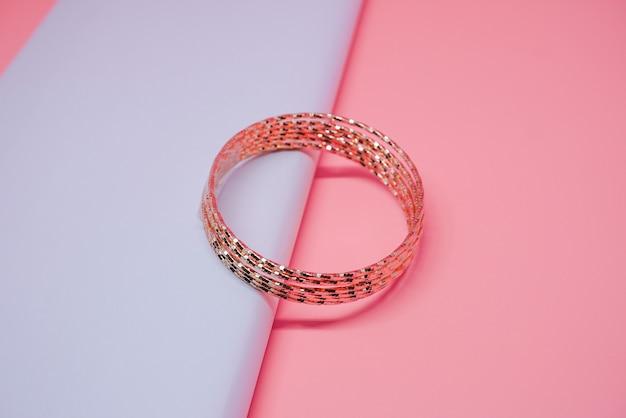 Foto de luxo feminino com pulseira de ouro em fundo pêssego