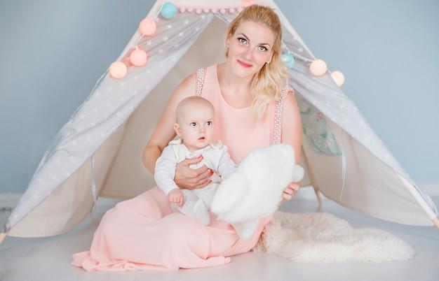 Foto de mãe brincando com seu filho em uma sala perto de uma barraca de crianças