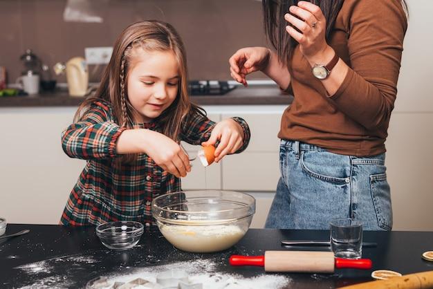 Foto de mãe e filha cozinhando na cozinha