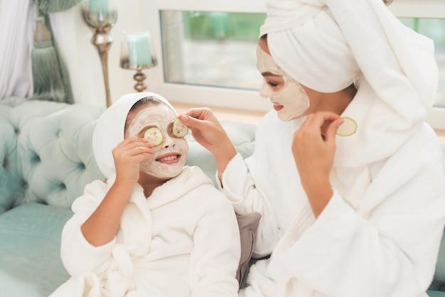 Foto de mãe e filha em roupões brancos