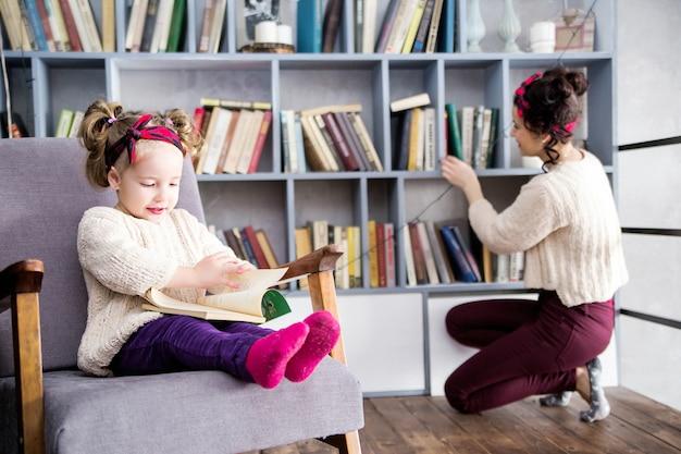 Foto de mãe e filha juntas no segundo andar de uma casa na biblioteca