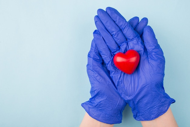 Foto de mãos com luvas segurando um coraçãozinho vermelho isolado