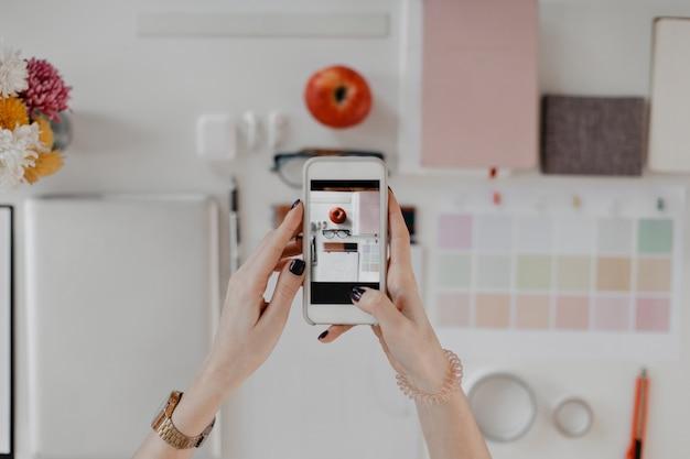 Foto de mãos femininas tirando retratos da área de trabalho com artigos de papelaria, óculos e maçã no smartphone