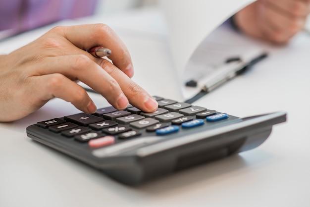 Foto de mãos segurando lápis e pressionando botões da calculadora sobre documentos