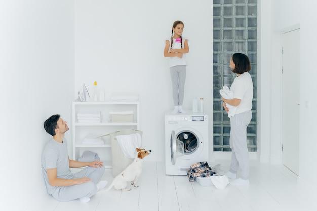 Foto de marido e mulher, seu cachorro e filha fazem trabalhos domésticos na lavanderia