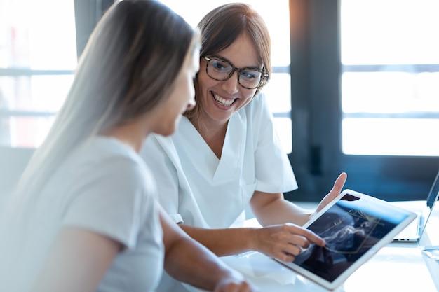 Foto de médico ginecologista jovem mostrando para bebê de ultrassom de mulher grávida com tablet digital em consulta médica.