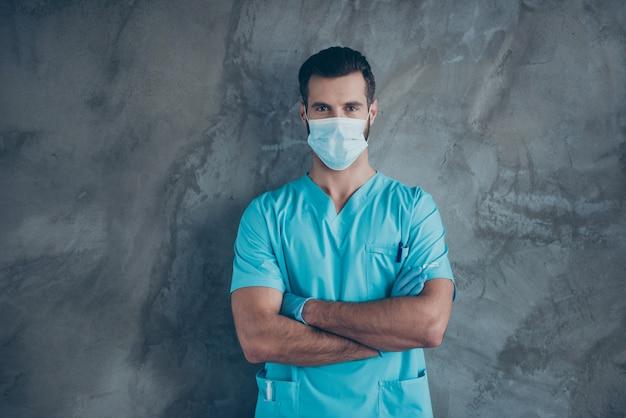 Foto de médico profissional qualificado usando máscara facial com braços cruzados especialista em cirurgia antes de iniciar a operação parede de concreto isolada de cor cinza