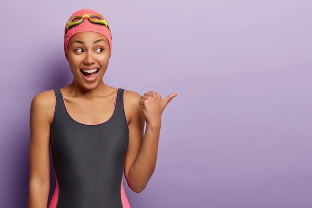 Foto de meio comprimento de nadador feliz usando óculos de natação, maiô