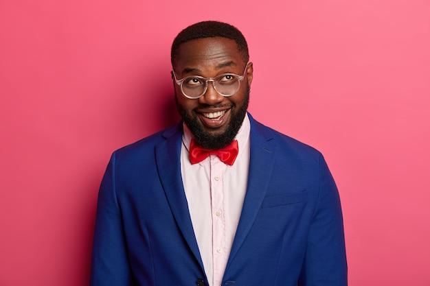 Foto de meio comprimento de um homem negro bonito parece com um sorriso acima, pensa em uma inicialização bem-sucedida, usa óculos transparentes, terno azul formal