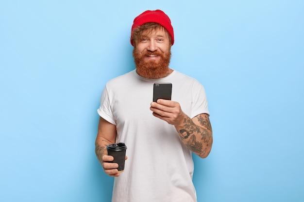 Foto de meio comprimento de um homem ruivo barbudo e alegre usa um chapéu estiloso, camiseta casual branca, segura o telefone celular, café para viagem, estando de bom humor, digita mensagens