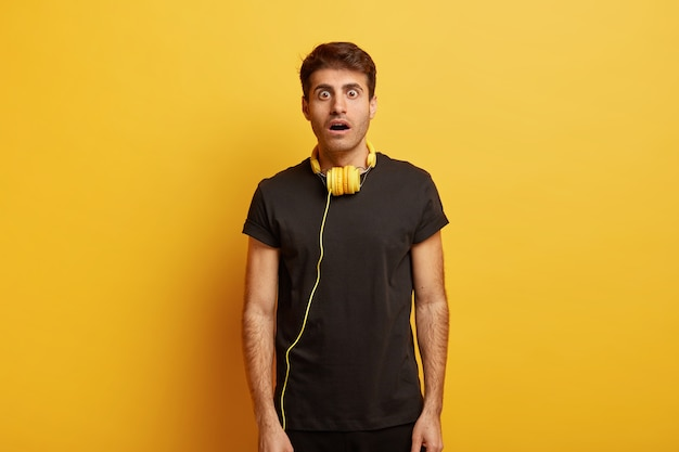 Foto de meio comprimento de um jovem branco surpreso com a boca bem aberta, vestindo uma camiseta preta casual