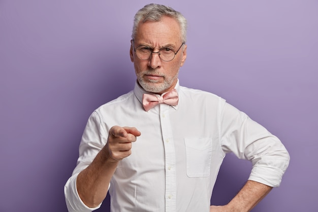 Foto de meio comprimento de um sério aposentado autoconfiante com cabelo grisalho, aponta o dedo da frente para a câmera, usa óculos, camisa branca elegante