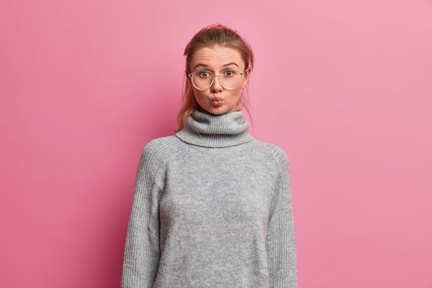 Foto de meio comprimento de uma bela jovem com os lábios dobrados, fazendo careta, indo para um clube inglês, usando grandes óculos óticos e um suéter cinza