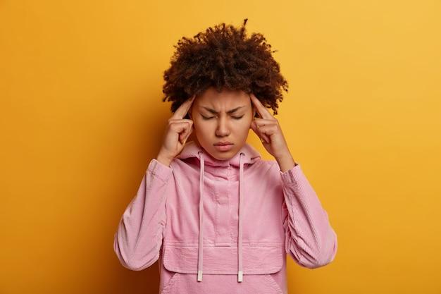 Foto de meio comprimento de uma mulher de pele escura angustiada que sente dor de enxaqueca ou dor de cabeça, toca as têmporas e aperta o rosto, fica cansada após uma reunião cansativa, tenta se concentrar, usa um moletom rosa