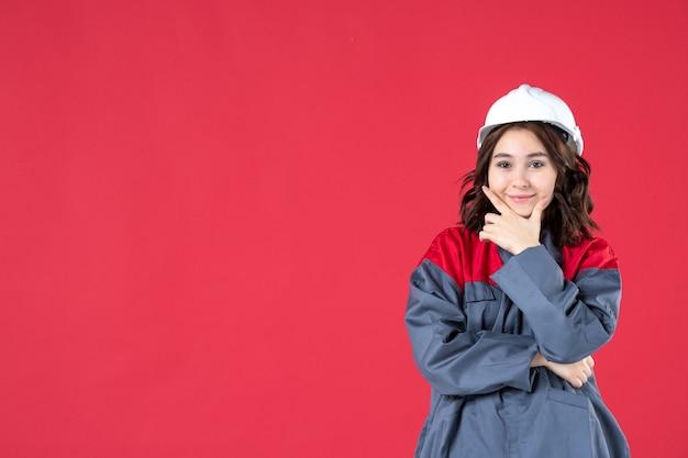 Foto de meio corpo da mulher feliz construtora de uniforme com capacete e concentrada em algo sobre fundo vermelho isolado