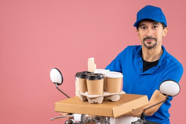 Foto de meio corpo de entregador confiante do sexo masculino usando chapéu, sentado na scooter, entregando pedidos