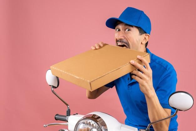 Foto de meio corpo de entregador louco e emocional do sexo masculino usando chapéu, sentado na scooter, entregando pedidos
