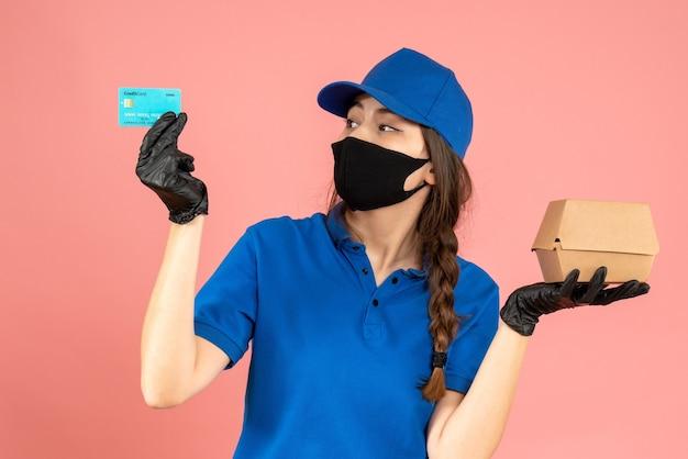 Foto de meio corpo de mensageira usando luvas pretas de máscara médica, segurando um cartão do banco e uma pequena caixa em fundo de pêssego pastel