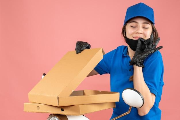 Foto de meio corpo de uma jovem mensageira sonhadora usando máscara médica e luvas, sentada na scooter, abrindo caixas em fundo de pêssego pastel