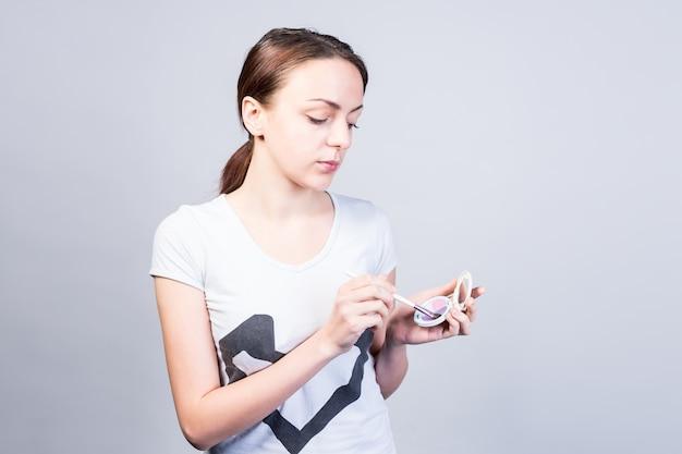 Foto de meio corpo de uma jovem séria em roupa casual segurando uma maquiagem contra um fundo cinza