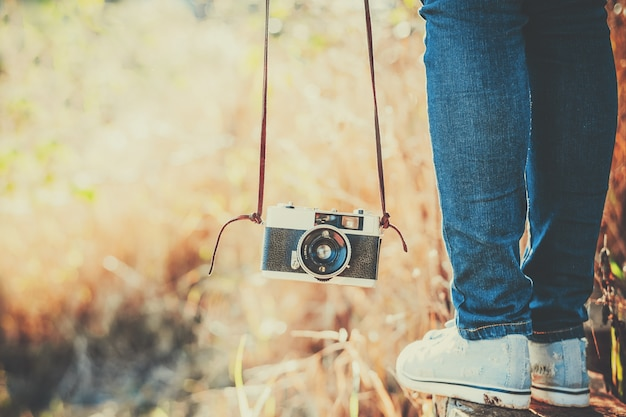 Foto de memórias e nostalgia. pés de mulher com câmera retro.