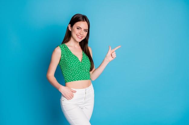 Foto de menina alegre positiva apontar o dedo indicador copyspace indica anúncios promoção feedback vestir roupa de boa aparência isolada sobre fundo de cor azul