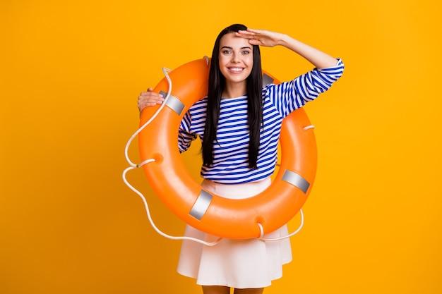 Foto de menina alegre positiva com bóia salva-vidas segurar mão rosto ver terra do oceano água usar camisa listrada saia vestido branco azul isolado sobre fundo de cor de brilho brilhante